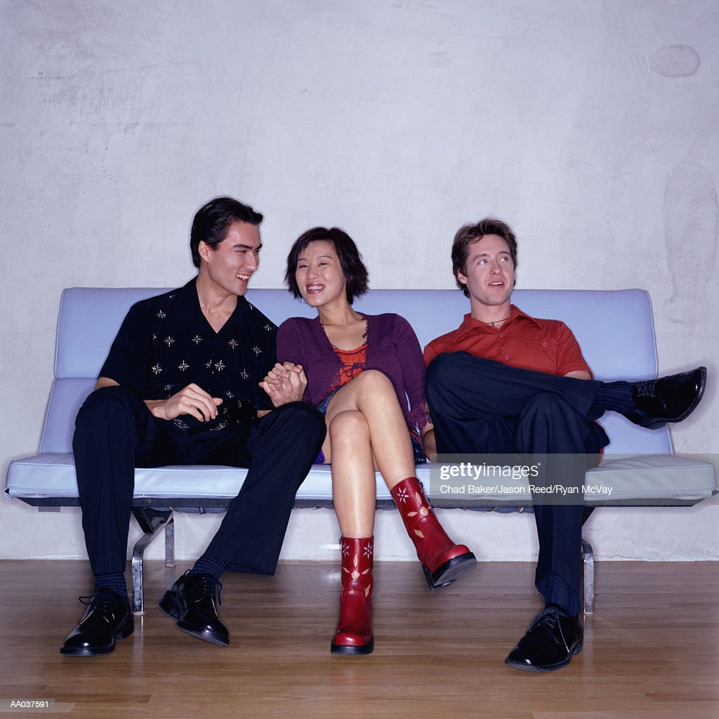 Three Young Adults Sitting on Retro Sofa Bench : Stock Photo
