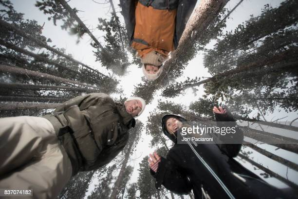 Three Young Adults Standing over the camera in a forest having fun and enjoying the snow