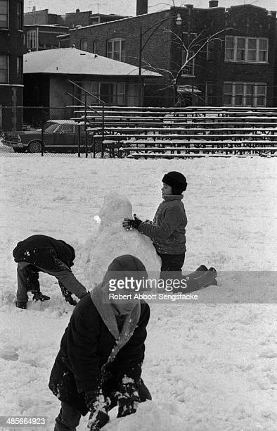 Three young African American children pack snow together to build a snowman in a Chicago playground Chicago Illinois mid to late 1960s