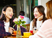 three happy beautiful young asian women sitting at table chatting talking relaxing in coffee shop or tea house.