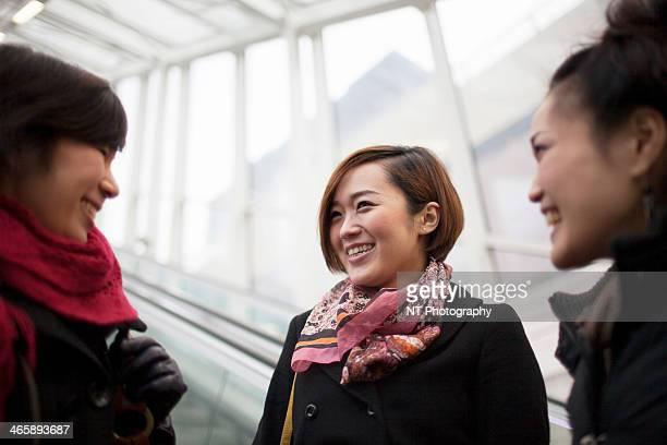 Three young Asian women talking