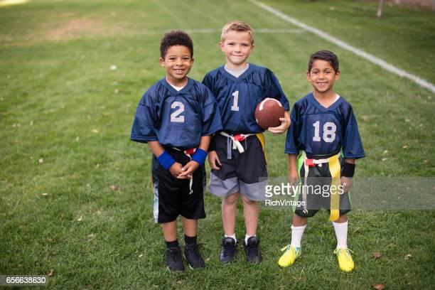 Three Young Boys and Teammates Play Flag Football