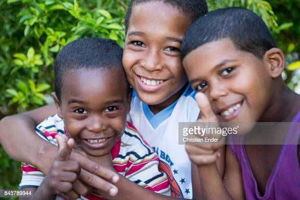 Santa Domingo Dominican Republic November 30 2012 Three young boys are smiling and pointing towards the camera in the poor neighbourhood 'Los...