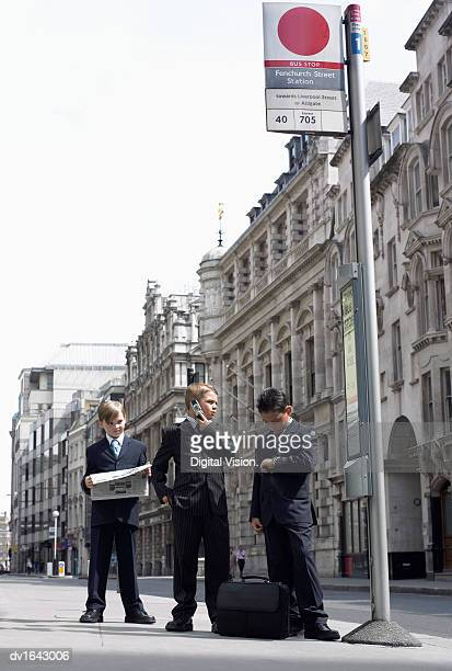 Three Young Boys Dressed as Businessmen Stand in Line at a Bus Stop, City of London