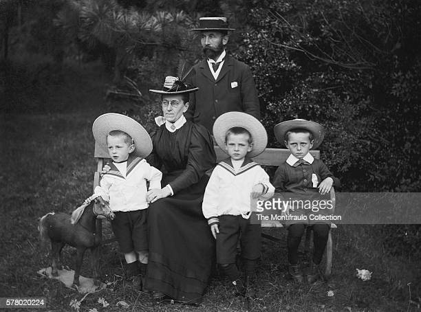 Three young boys wearing large brimmed boater hats one holding a toy pull along horse sitting on garden bench beside a woman wearing a feathered...