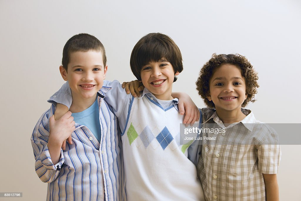 Three young boys with arms around each other : Stock Photo