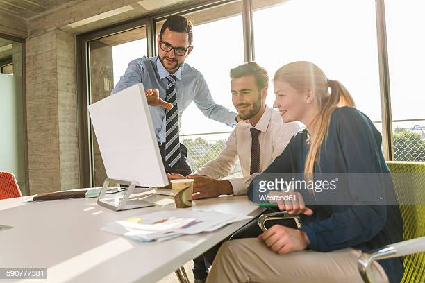 Three young business people in conference room looking at monitor