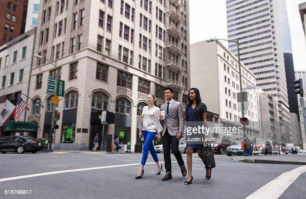 Three young business people stride across street