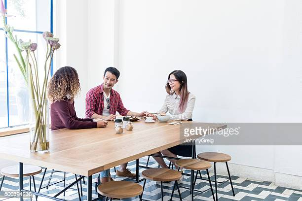 Three young businesspeople at table in cafe talking, with coffee