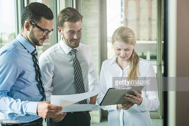 Three young businesspeople looking at documents and digital tablet