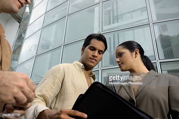 Three young businesspeople outdoors, with one man handing woman portfolio, close-up, high angle view