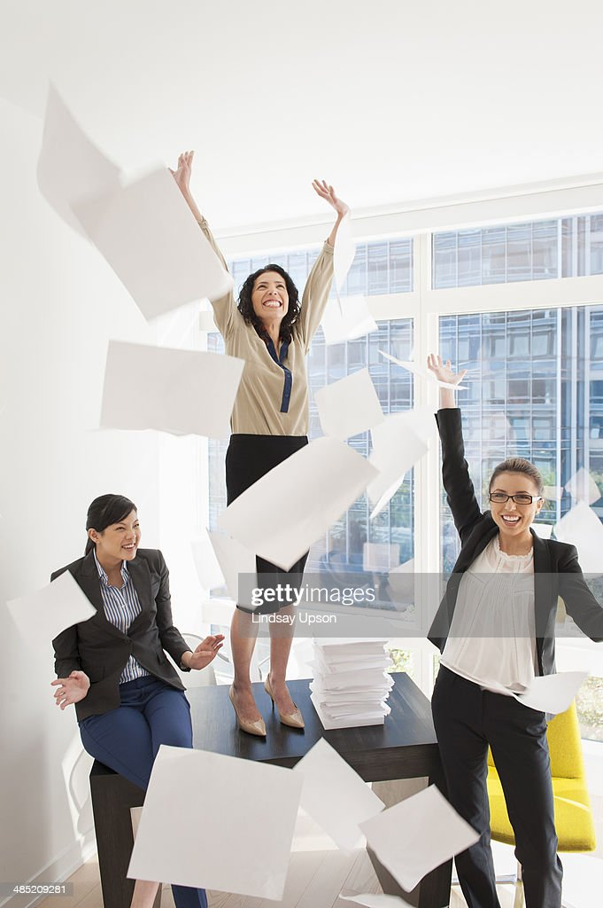 Three young businesswoman throwing papers mid air : Stock Photo