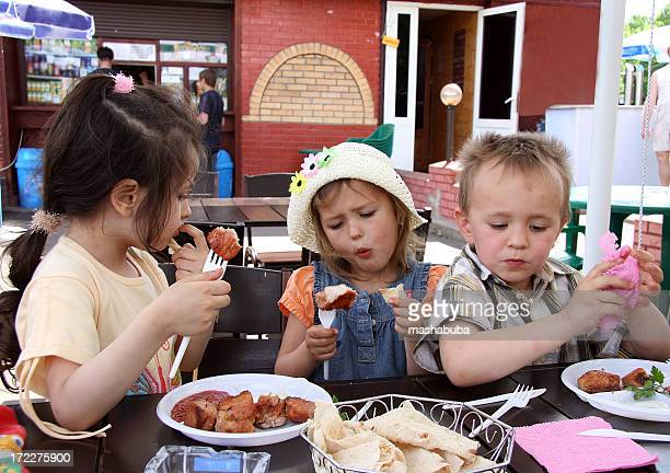 Three young Caucasian children in a cafee