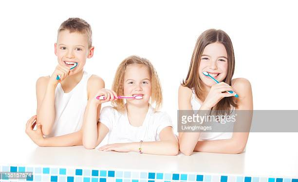 Three young children brushing their teeth