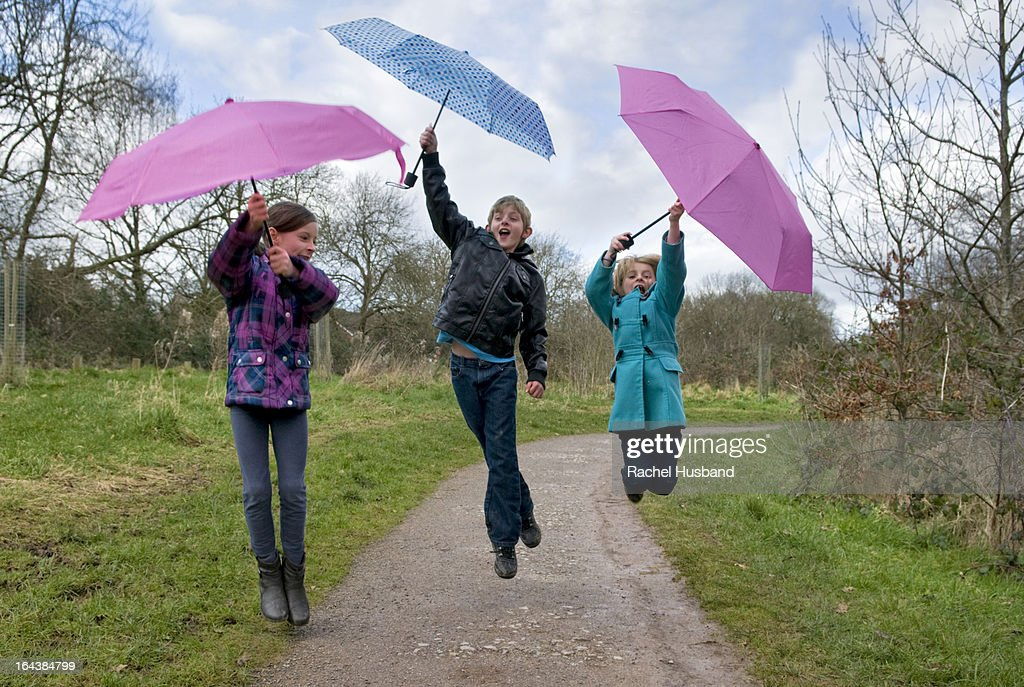 Three young children jumping with umbrellas : Stock Photo