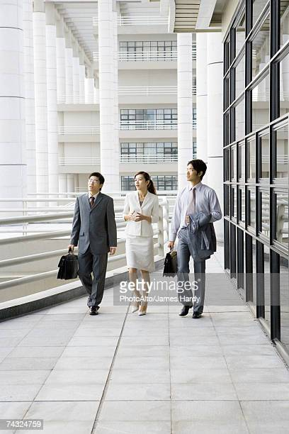 Three young executives walking side by side next to office building