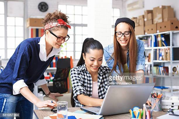 Three young female colleagues having fun at workplace