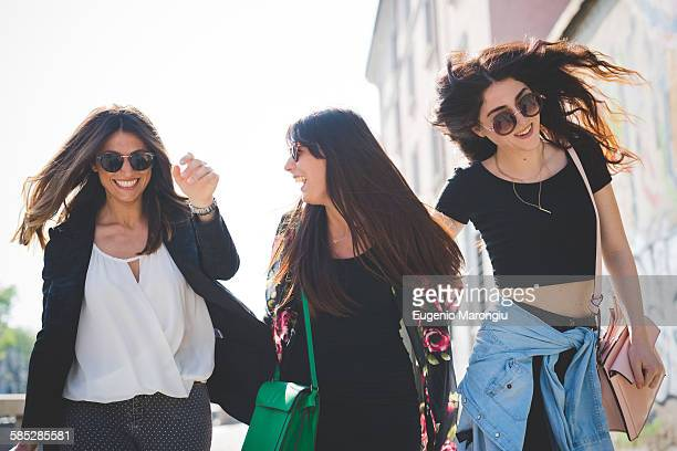 Three young female friends strolling and fooling around