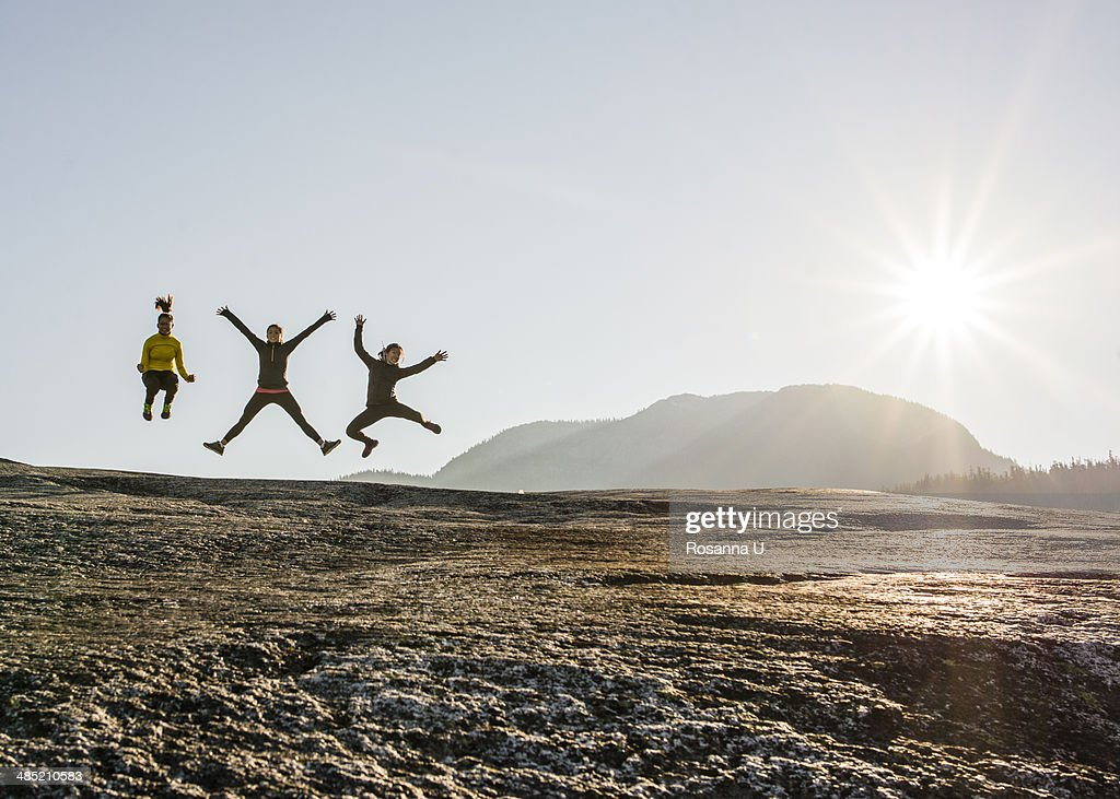 Three young female hikers jumping mid air on rock, Squamish, British Columbia, Canada : Stock Photo