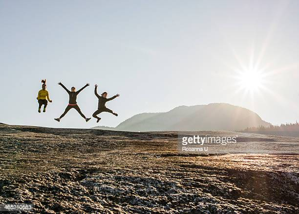 Three young female hikers jumping mid air on rock, Squamish, British Columbia, Canada