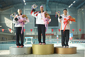 Three young female swimmers displaying medals, trophies and flowers