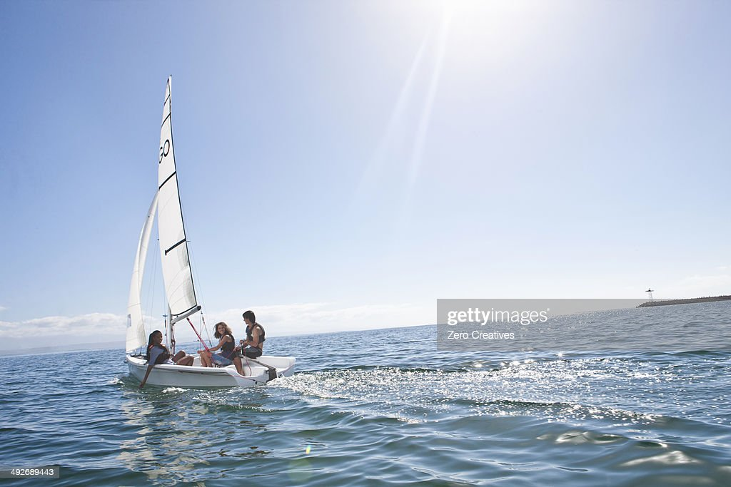 Three young friends sailing out from harbor