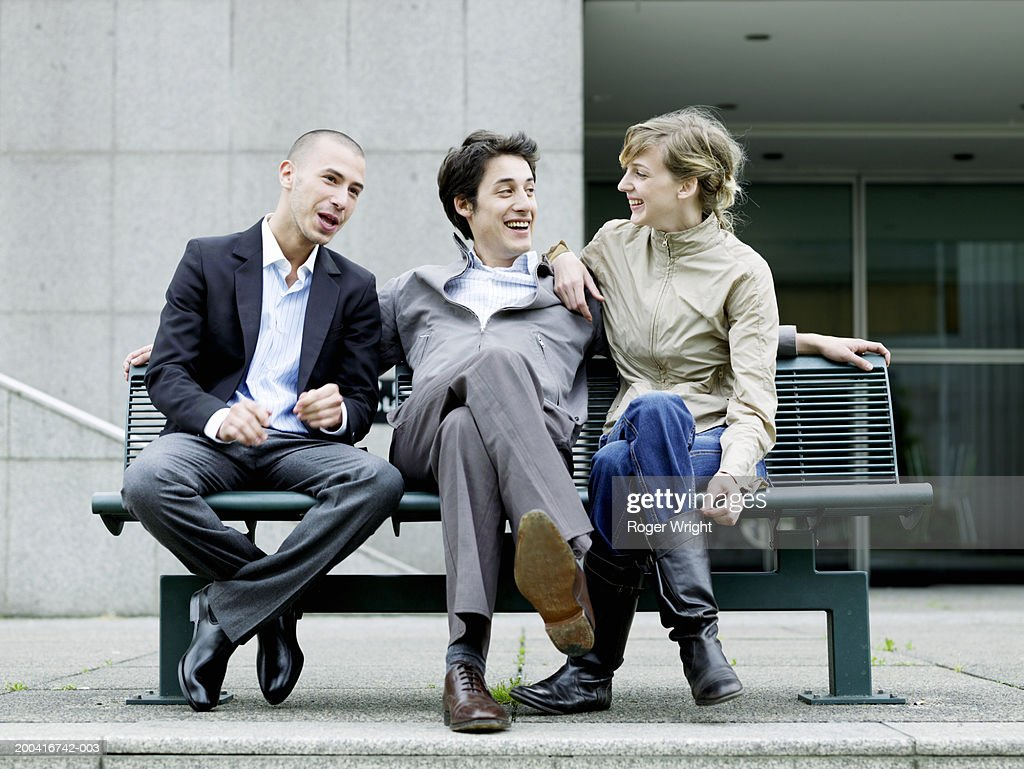 Three young friends sitting on bench, laughing, low angle view : Stock Photo