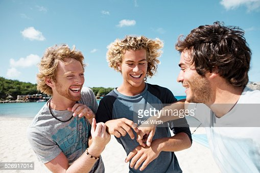 Three young friends smiling on beach : Foto stock