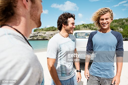 Three young friends standing on beach : Stock Photo
