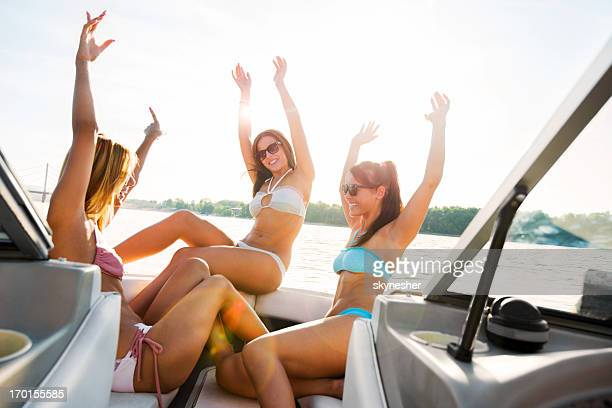 Three young girls in bikini on speedboat with raised hands.