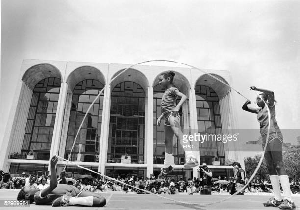Three young girls jump rope double dutch style on stage in front of an audience outside the Metropolitan Opera House in the Lincoln Center Fountain...