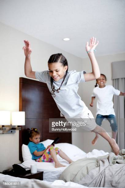 Three young girls jumping on a bed