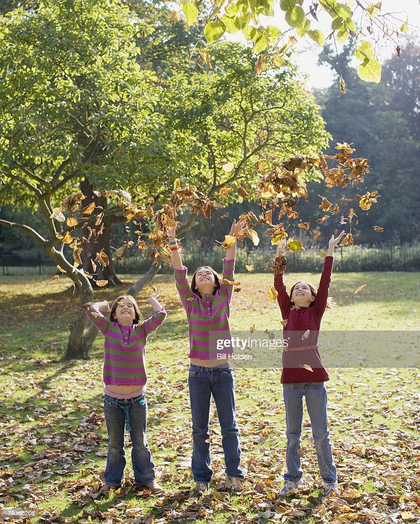 Three young girls outdoors throwing leaves in the air : Stock Photo