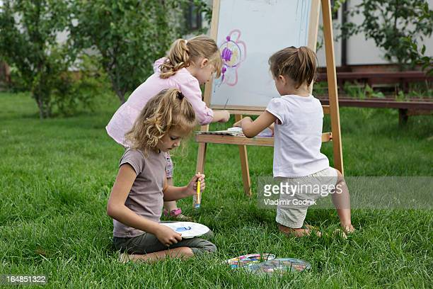 Three young girls painting in the backyard
