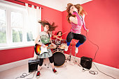 Three young girls playing in a rock band