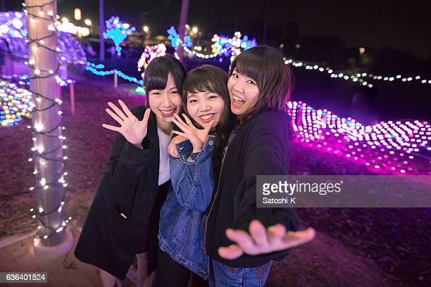 Three young girls playing together in Christmas lights