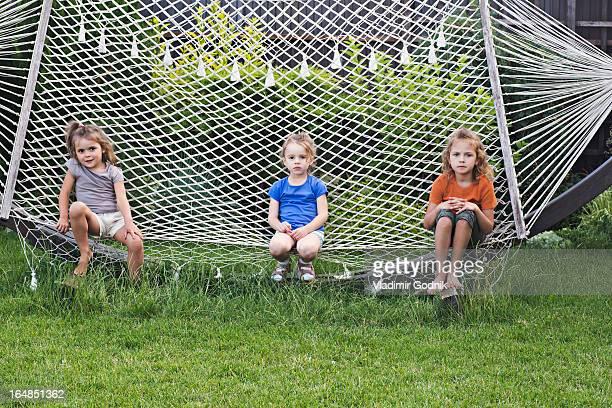 Three young girls sitting on a hammock