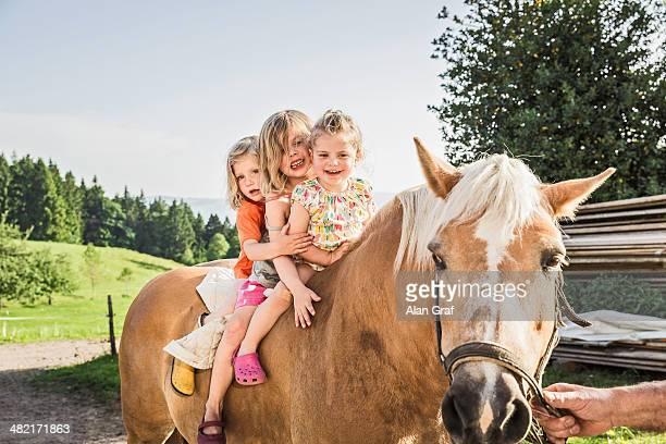 Three young girls sitting on palomino horse