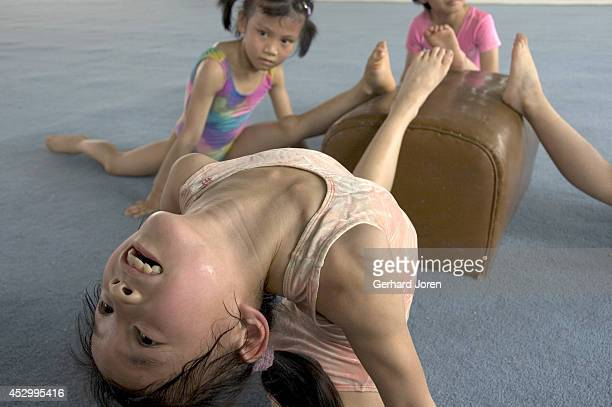 Three young girls stretch their backs during a gymnastics training session at the Wei Lun Sports and Athletics School Established in the mid 50s the...