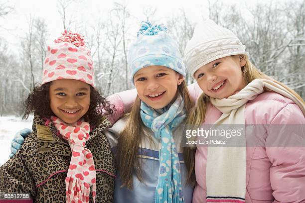 Three young girls with arms around each other