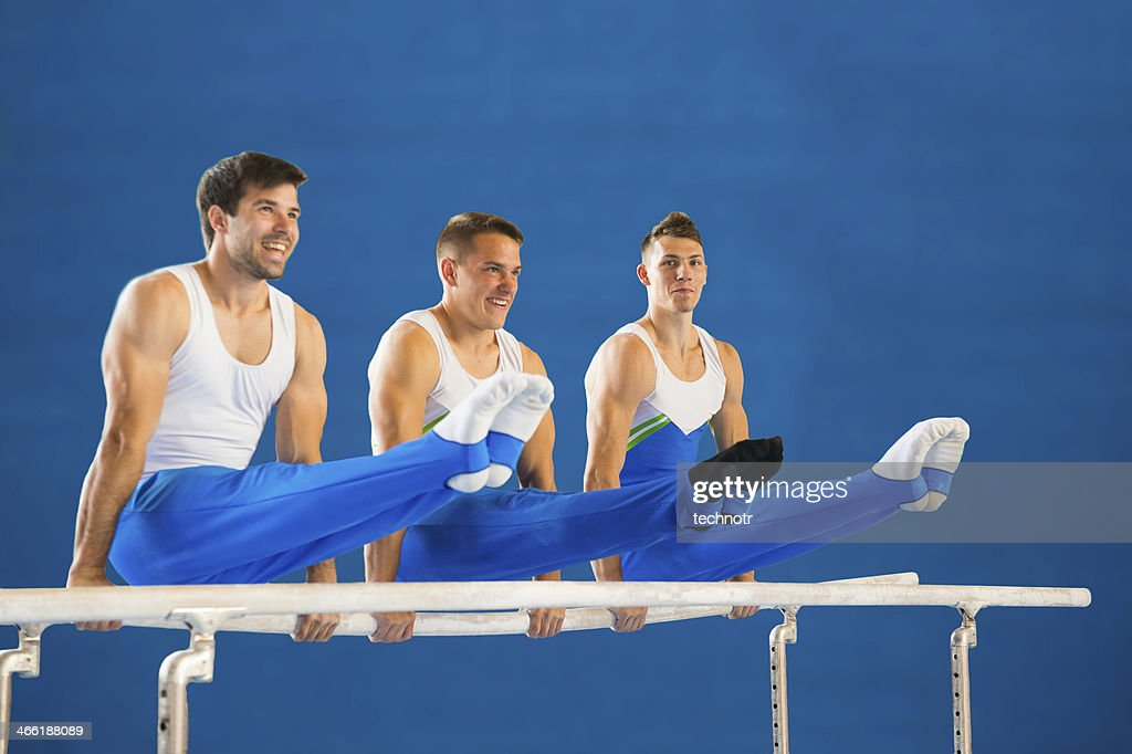Three young gymnasts posing on the parallel bars