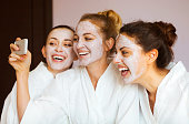 Three young happy women with face masks taking selfie at spa resort. Friendship and wellbeing concept