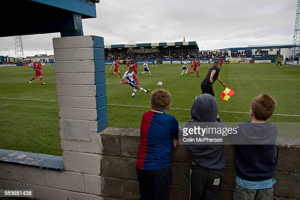 Three young home supporters watching the action from the terracing at Barrow AFC's Furness Building Society Stadium during the Barrow v Newport...