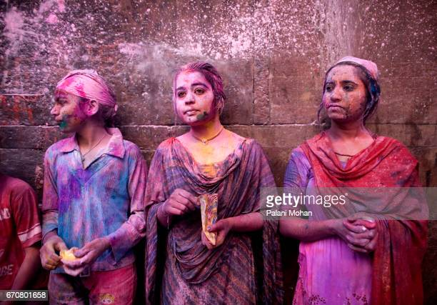 Three young Indian girls are sprayed with colour power at the Sri Banke Bihari Temple as they celebrate Holi the festival of colour March 22 2008 in...