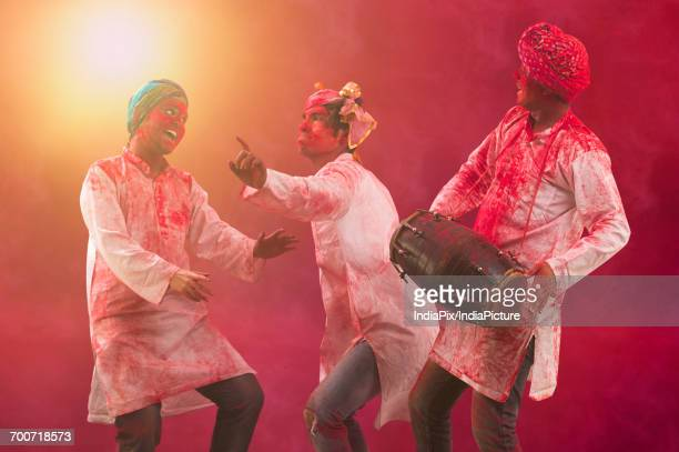 Three Young Indian men With Colored Face Dancing During Holi Color festival