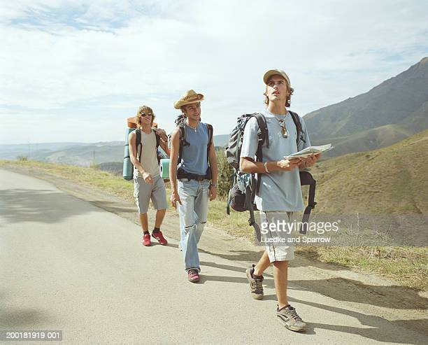 Three young male backpackers walking along road