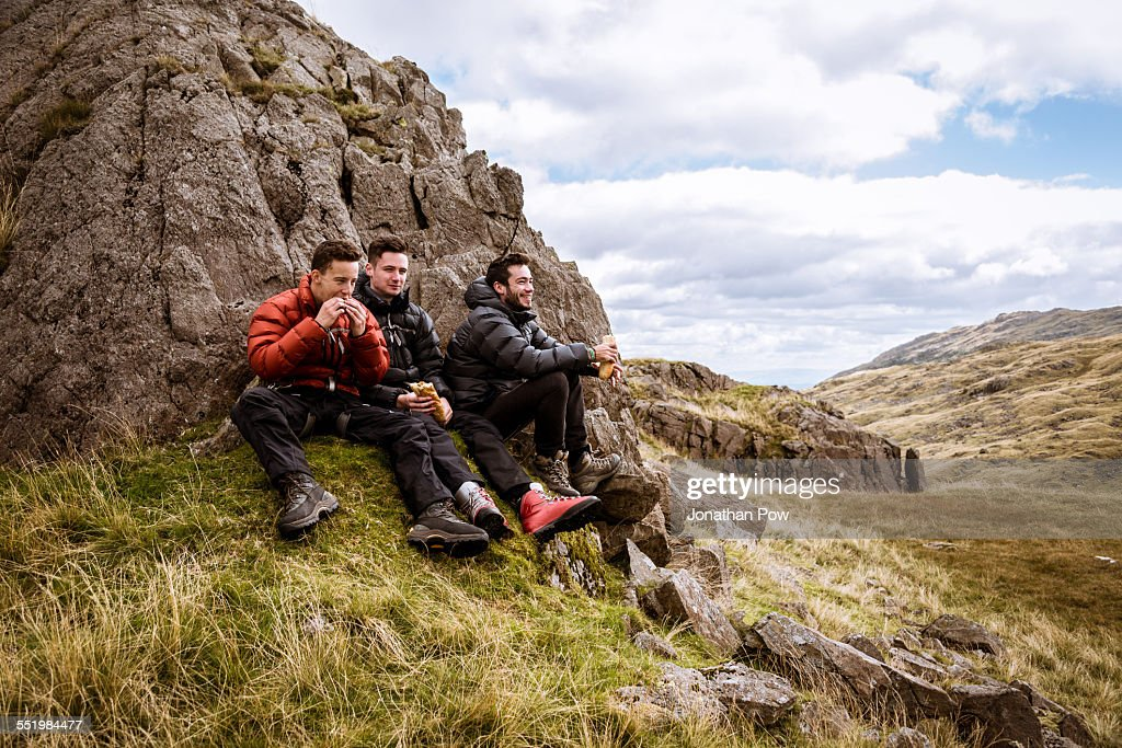 Three young male hiking friends eating sandwiches, The Lake District, Cumbria, UK : Stock Photo
