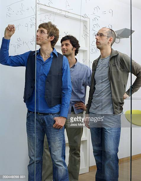 Three young male office workers, one writing equation on window
