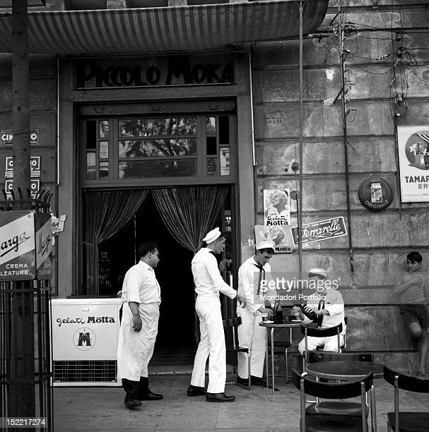 Three young marines are drinking beer in front of the small café 'Piccolo Moka' The barman and a boy leant against a wall are looking at them Palermo...