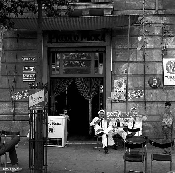 Three young marines are drinking beer in front of the small café 'Piccolo Moka' Two boys are looking at them Palermo 1956